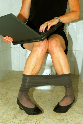Crazy Busy - Woman sitting on the toilet with her laptop computer, still working